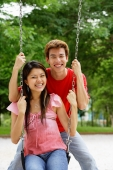 Couple in playground, woman sitting on swing, man behind her, looking at camera - Alex Microstock02