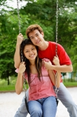 Couple in playground, woman sitting on swing, man behind her, smiling at camera - Alex Microstock02