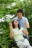 Woman sitting on swing, man behind her, pushing swing - Alex Microstock02