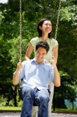 Man sitting on swing, woman standing behind him - Alex Microstock02
