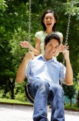 Man sitting on swing, woman standing behind him, laughing - Alex Microstock02