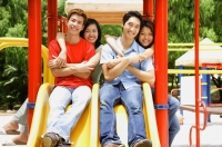Couples in playground, smiling at camera, portrait - Alex Microstock02