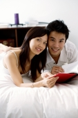 Couple lying on bed, holding book, looking at camera - Alex Microstock02