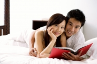 Couple lying on bed, holding book, smiling at camera - Alex Microstock02