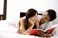Couple lying on bed, holding book, smiling at each other - Alex Microstock02