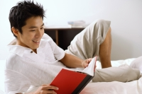 Man lying on bed, reading book, smiling - Alex Microstock02