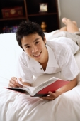 Man lying on bed, holding book, smiling at camera - Alex Microstock02