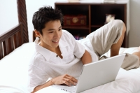 Man lying on bed, using laptop, smiling - Alex Microstock02