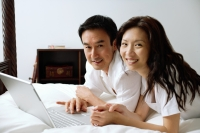 Couple lying on bed, using laptop, smiling at camera - Alex Microstock02