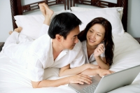 Couple lying side by side on bed, using laptop - Alex Microstock02