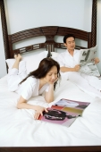 Couple on bed, woman reading magazine, man reading newspaper - Alex Microstock02