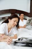 Couple in bedroom, woman reading magazine, man reading newspaper - Alex Microstock02