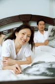 Couple in bedroom, woman smiling at camera, man reading newspaper in the background - Alex Microstock02