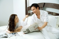 Couple in bedroom, man showing woman newspaper - Alex Microstock02