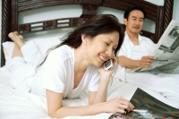 Couple in bedroom, woman reading magazine and using mobile phone, man reading newspaper - Alex Microstock02
