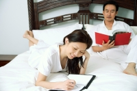 Couple in bedroom, woman writing in diary, man reading book - Alex Microstock02