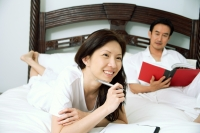 Couple in bedroom, woman holding pen, man reading book - Alex Microstock02