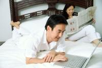 Couple in bedroom, man using laptop, woman reading newspaper - Alex Microstock02