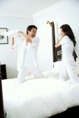 Couple in bedroom, having pillow fight - Alex Microstock02