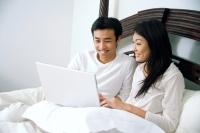 Couple in bedroom, using laptop - Alex Microstock02