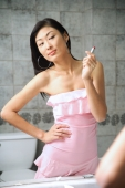 Woman looking at bathroom mirror, holding lipstick, hand on hip - Alex Microstock02