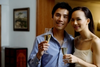 Couple holding champagne glasses, smiling at camera - Alex Microstock02