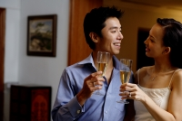 Couple standing face to face, holding champagne glasses - Alex Microstock02