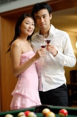 Couple standing side by side, holding wine glasses, looking at camera - Alex Microstock02