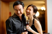 Couple holding wine glasses, laughing - Wang Leng