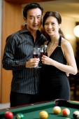 Couple holding wine glasses, standing side by side, smiling at camera - Wang Leng