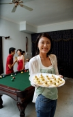 Woman holding tray of appetizers, smiling at camera, people in the background - Alex Microstock02
