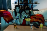 Three young women sitting on sofa in living room, watching TV - Alex Microstock02