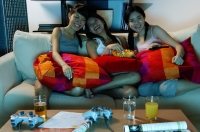 Three young women in living room, watching TV - Alex Microstock02