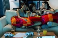 Three young women in living room, sitting on sofa - Alex Microstock02