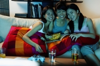 Three young women in living room, sitting on sofa, smiling at camera - Alex Microstock02