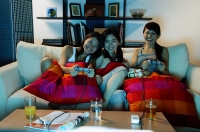 Three young women in living room, playing video games - Alex Microstock02