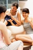 Three young women on sofa, talking - Alex Microstock02