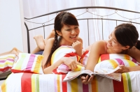Two young women lying on bed, looking at magazine - Alex Microstock02