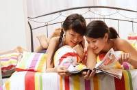 Two young women lying on bed, going through magazine - Alex Microstock02