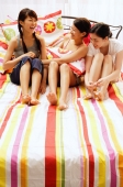 Three young women sitting on bed - Alex Microstock02