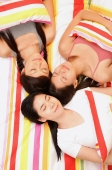 Three young women lying on bed, high angle view - Alex Microstock02