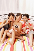 Three young women sitting on bed, side by side, applying make-up - Alex Microstock02