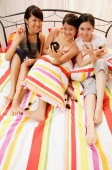 Three young women sitting on bed, side by side, looking at camera - Alex Microstock02