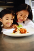 Two children looking at a plate of food, smiling - Alex Microstock02