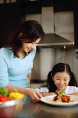 Mother and daughter looking at plate of food - Alex Microstock02