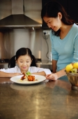 Mother and daughter looking at plate of food, smiling - Alex Microstock02