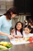 Mother cutting vegetables in kitchen, daughters standing next to her - Alex Microstock02