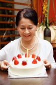 Mature woman looking at birthday cake, smiling - Alex Microstock02