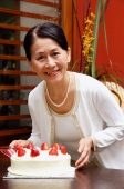 Mature woman holding birthday cake, looking at camera - Alex Microstock02