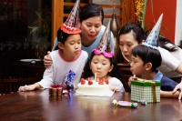 Family celebrating birthday, blowing candle - Alex Microstock02